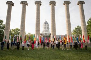 Image of writers holding flags from their home countries with Jesse Hall in the background
